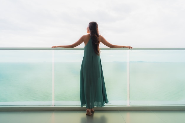 Beautiful portrait young asian woman happy smile relax at balcony with sea ocean