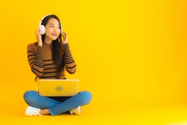 La giovane donna asiatica del bello ritratto si siede sul pavimento con il computer portatile e la cuffia sulla parete gialla