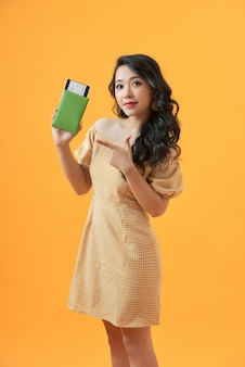 美しい肖像画の若いアジアの女性は、休暇中の旅行夏の旅行でパスポートを保持し、ポインティング自信を持って笑顔