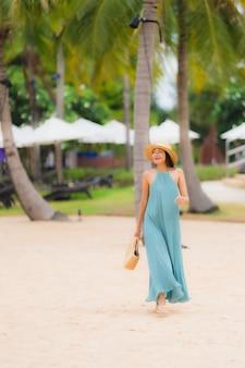 Il sorriso felice delle giovani donne asiatiche del bello ritratto si rilassa intorno all'oceano del mare della spiaggia