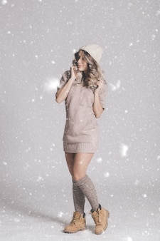 Beautiful portrait of young attractive woman in knitted clothes on snowy background
