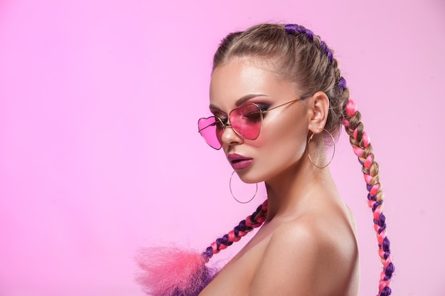 Beautiful portrait of a young girl. professional make-up and hairstyle made of colored plaits.