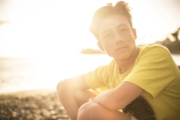 Beautiful portrait young handsome people male teenager sitting at the beach with sunset sun in backlight - outdoor leisure activity concept