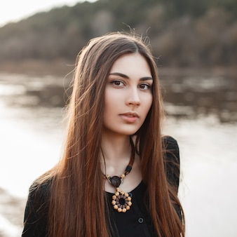 Beautiful portrait of a young pretty girl with long hair near the water