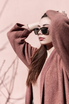 화창한 날에 분홍색 벽 근처 야외 코트에서 유행 선글라스에 아름 다운 초상화 젊은 여자. 섹시한 입술로 깨끗한 피부를 가진 사랑스러운 소녀는 빈티지 건물 근처에 서있는 고급스러운 머리카락을 곧게 만듭니다.