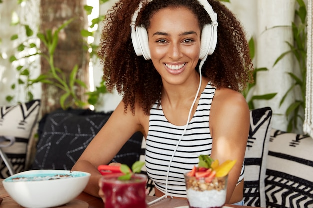Beautiful positive african american woman enjoys listening music in headphones, spends leisure time at loft cafeteria with cocktail, has break after work, demonstrates pleasant smile.