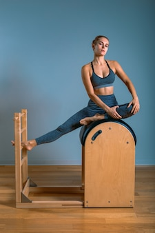 Beautiful positive blond woman is being prepared performing pilates exercise, training on barrel equipment. fitness concept, special fitness equipment, . copy space, sport banner for advertising.
