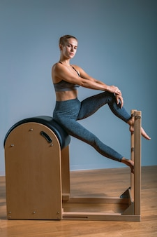 Beautiful positive blond woman is being prepared performing pilates exercise