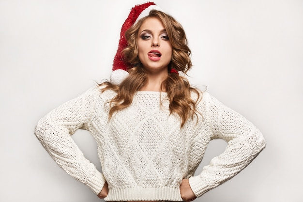 Beautiful positive blonde in a sweater and festive cap