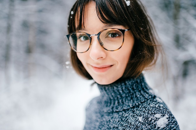 Beautiful positive  brunette girl in trendy glasses looking at camera. with snow on hair.