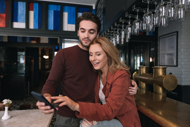 Beautiful positive couple using phone and looking down