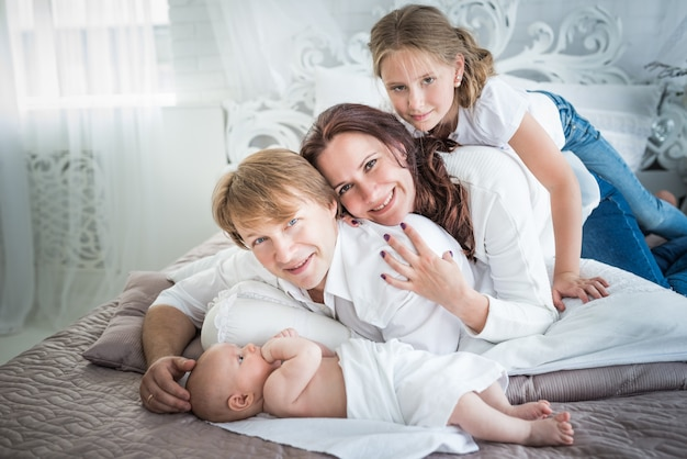 Красивая позитивная семья, мама, папа, старшая дочь и новорожденный брат в красивой и стильной комнате