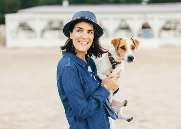 Beautiful positive female in stylish hat and denim shirt holds her pet on hands, looks with smile aside as notices her friend, walk outdoor. people, animals, lifestyle and relaxation concept