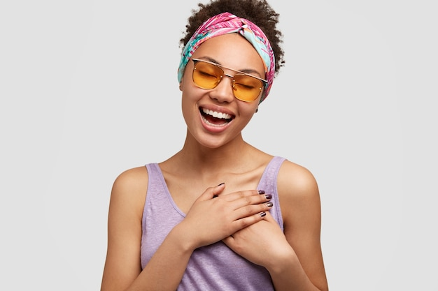 Beautiful positive friendly looking female keeps both hands on chest, express gratitude to sister for help and advice, wears fashionale shades and sunglasses, isolated over white wall