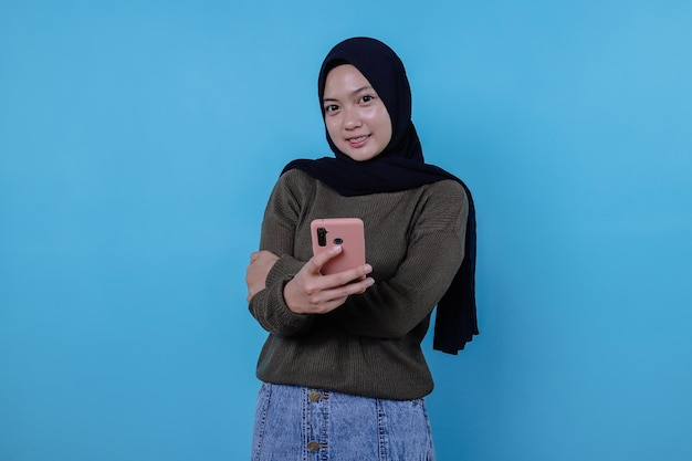 히잡을 쓴 아름다운 긍정적이고 친근한 젊은 여성이 휴대폰을 들고 고맙고 감사하게 생각하는 사랑스러운 진실한 미소