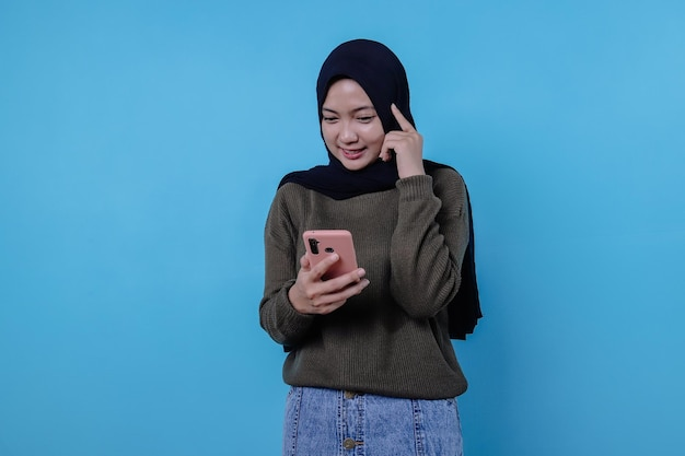 Beautiful positive friendly-looking young woman wearing hijab with lovely sincere smile feeling thankful and grateful holding mobile phone