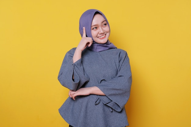 Beautiful positive friendly-looking young woman wearing hijab with lovely sincere smile feeling thankful and grateful thinking gesture