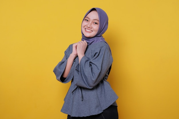 Beautiful positive friendly-looking young woman wearing hijab with lovely sincere smile feeling thankful and grateful