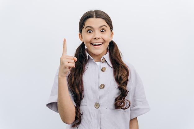 아름답고 긍정적인 소녀가 손가락을 들어 올렸습니다. 흰색 배경에 있는 소녀는 좋은 아이디어를 가지고 있습니다