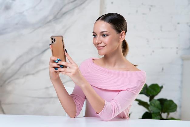 Красивая позитивная девушка, молодая довольно счастливая милая женщина смотрит на экран своего мобильного телефона