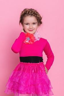 Красивая позитивная маленькая блондинка с вьющимися волосами в стильном повседневном розовом платье и сандалиях гуляет и улыбается на фоне серой стены. летняя мода для детей концепции