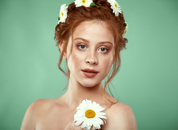 Beautiful positive redheaded girl with a chamomile crown on her head