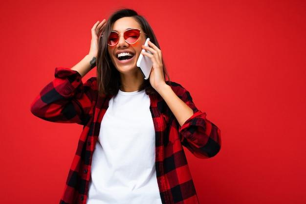 携帯電話で話している赤い背景の上に分離されたスタイリッシュな赤いシャツ白いtシャツと赤いサングラスを身に着けている美しいポジティブな笑顔の幸せな若いブルネットの女性。