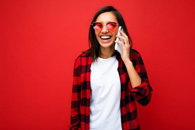 カメラを見て携帯電話で話している赤い背景の上に分離されたスタイリッシュな赤いシャツ白いtシャツと赤いサングラスを身に着けている美しいポジティブな笑顔の若いブルネットの女性。