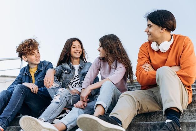 아름답고 긍정적인 십대들은 야외에서 서로 행복하게 의사소통합니다. 10대들은 벤치에 앉아 이야기를 나눈다.