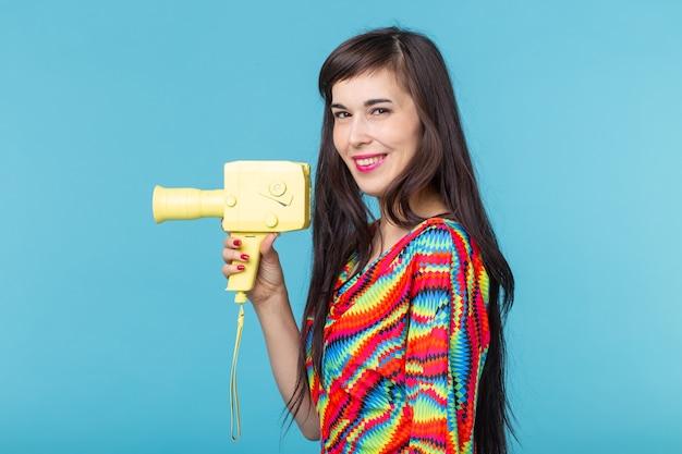 彼女の手で青い壁にポーズをとって黄色のビデオカメラのモデルを保持している美しいポジティブな若いブルネットの女性。ホームビデオ録画のコンセプト。