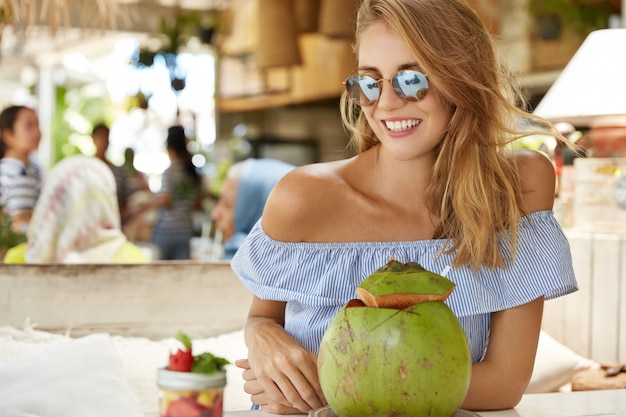 Beautiful positive young female in sunglasses, enjoys coconut cocktail in outdoor cafe, smiles pleasantly, rejoices having summer holidays in tropical place, tastes exotic beverage and dessert