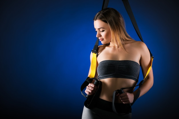 Beautiful positive young girl fitness model posing in studio holding on to hanging straps