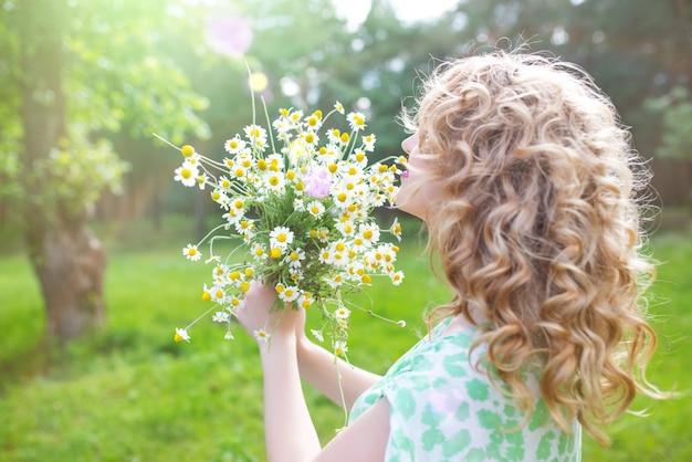 녹색 드레스에 아름 다운 긍정적 인 젊은 여자는 녹색 잔디에 누워