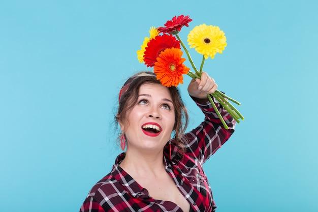 격자 무늬 셔츠에 아름 다운 긍정적 인 젊은 여자와 파란색 표면 위에 포즈 아름 다운 밝은 거베라 꽃을 스니핑 붕대