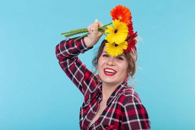 격자 무늬 셔츠에 아름다운 긍정적 인 젊은 여자와 아름다운 밝은 거베라 스니핑 붕대