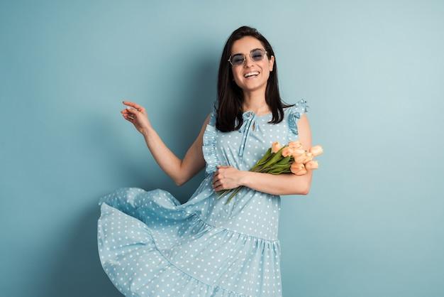 파란색 벽에 포즈를 취하는 그녀의 손에 폴카 도트 드레스와 꽃에 아름답고 긍정적 인 젊은 여성