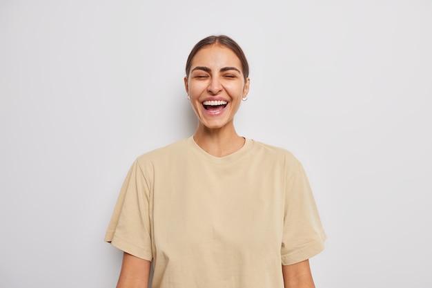 검은 머리 미소를 가진 아름다운 긍정적인 젊은 여성은 캐주얼한 갈색 티셔츠를 입고 흰 벽에 기대어 포즈를 취하는 것을 매우 기쁘게 생각합니다