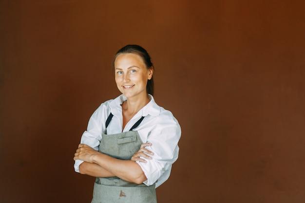 Красивая женщина-гончар лепит из глиняного горшка скульптор работает из глины на гончарном круге