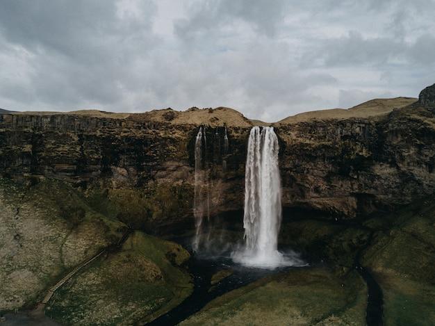 曇り空の下、川を流れる美しい迫力の滝