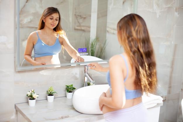 Красивая беременная женщина брюнет в ванной комнате перед зеркалом. гигиена. уход за собой во время беременности. доброе утро. фото высокого качества