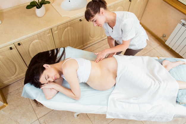 Beautiful pregnant brunette woman with long hair enjoying back massage in a beautician room