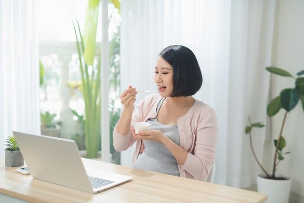 美しい妊娠中のビジネスウーマンは、自宅の職場に座ってヨーグルトを食べて笑っています