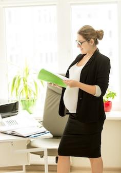 オフィスでドキュメントとファイルを保持している美しい妊娠中の実業家