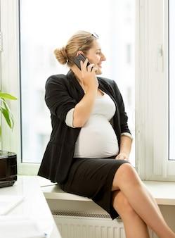 Красивая беременная бизнесвумен сидит на подоконнике и разговаривает по телефону