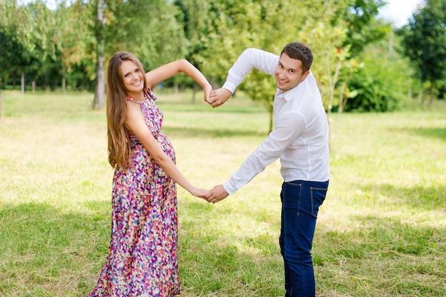 Красивая беременная пара счастлива вместе, ожидая ребенка. мужчина и женщина, прогулки в парке, показывая сердце с руками. разделите любовь и семью, понятие любви.