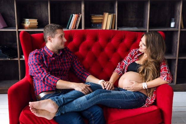 Красивая беременная пара отдыха на диване у себя дома вместе. счастливая семья, мужчина и женщина ожидают ребенка.