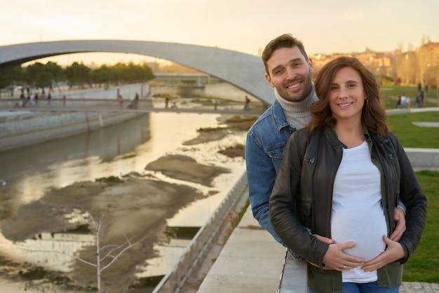 아름 다운 임신 부부. 젊은 성인. 남자는 그녀의 아내를 잡고 그녀의 임신 배를 만지고. 가족 초상화.