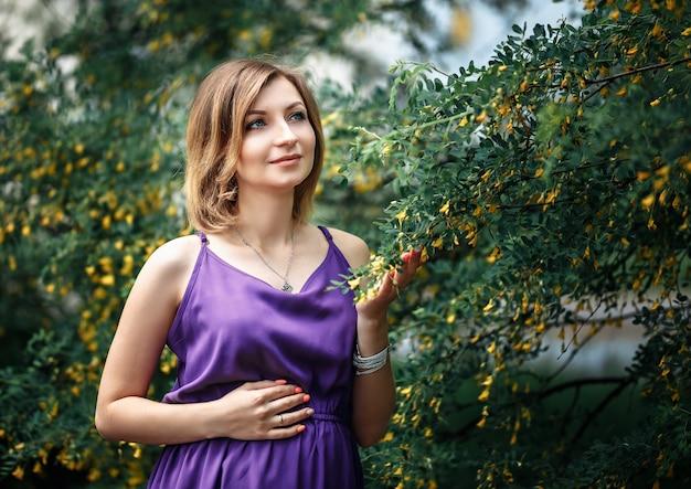 Beautiful pregnant european woman in purple violet dress, standing near bushes of acacia