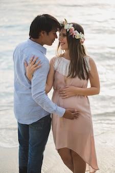Красивая беременная девушка и мужчина на пляже