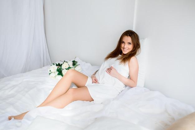 白いドレスと花の花束を持つ美しい妊娠中の女の子。